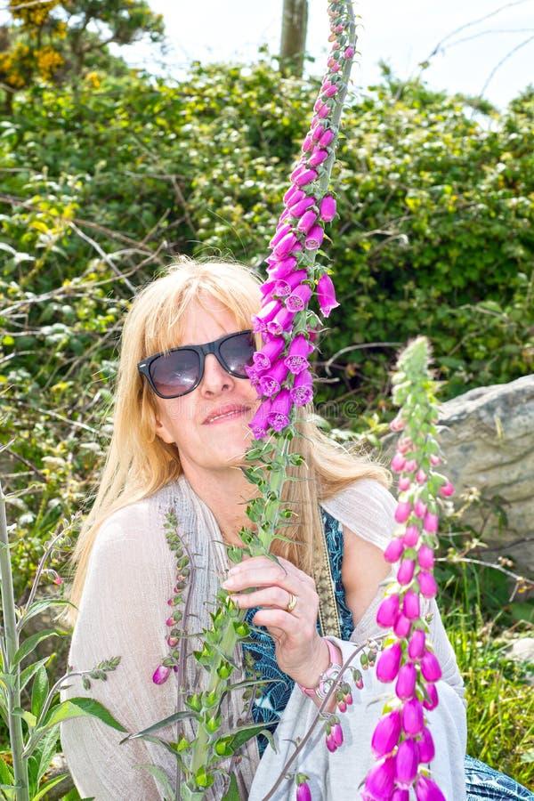 Kobieta wącha dzikie lis rękawiczki fotografia stock