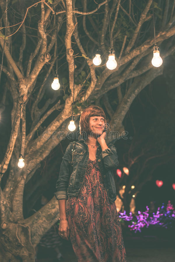 Kobieta wśród dekoracyjnego plenerowego sznurka zaświeca obwieszenie na drzewie w parku przy nighttime bali piękny Indonesia wysp zdjęcia stock