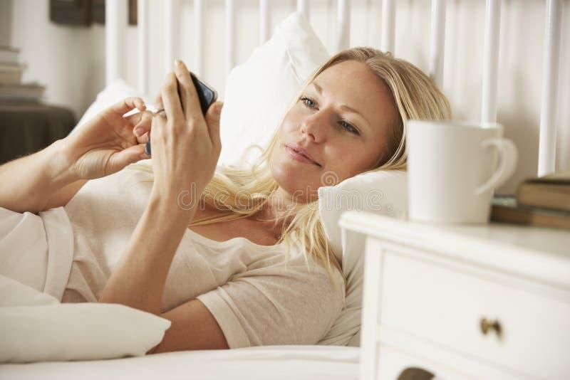 Kobieta W łóżku Texting Na telefonie komórkowym W Domu zdjęcie stock