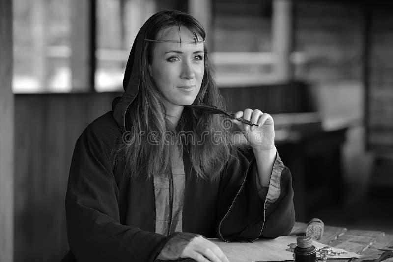 Kobieta w średniowiecznej pelerynie siedzi z piórem obrazy royalty free