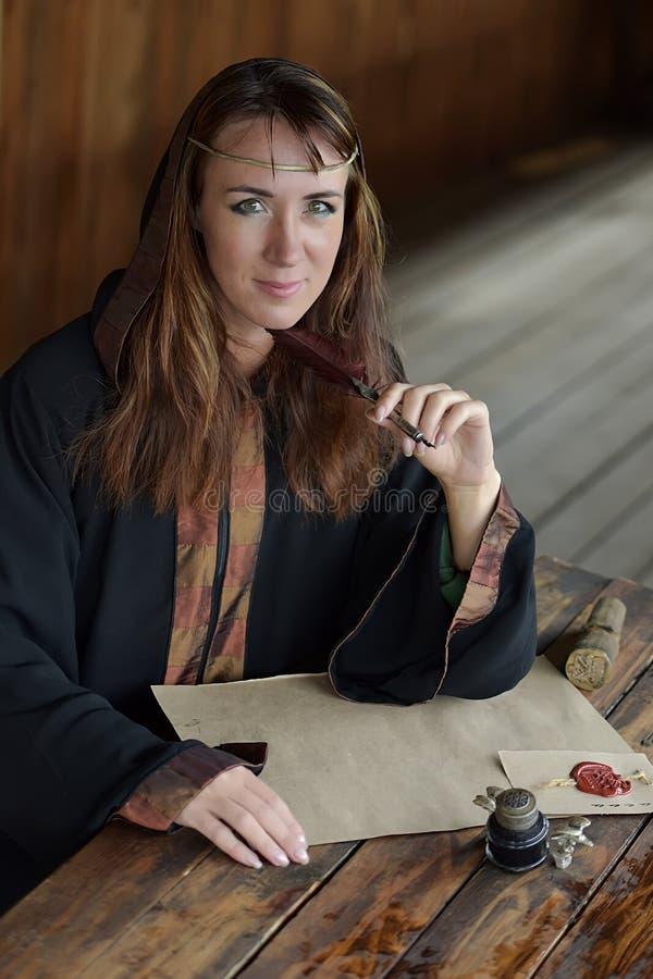 Kobieta w średniowiecznej pelerynie siedzi z piórem zdjęcie royalty free