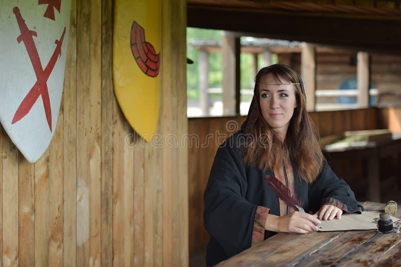 Kobieta w średniowiecznej pelerynie siedzi z piórem fotografia royalty free