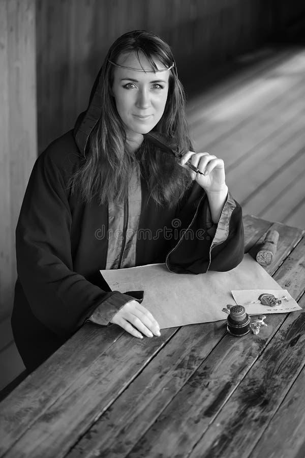 Kobieta w średniowiecznej pelerynie siedzi z piórem obraz stock