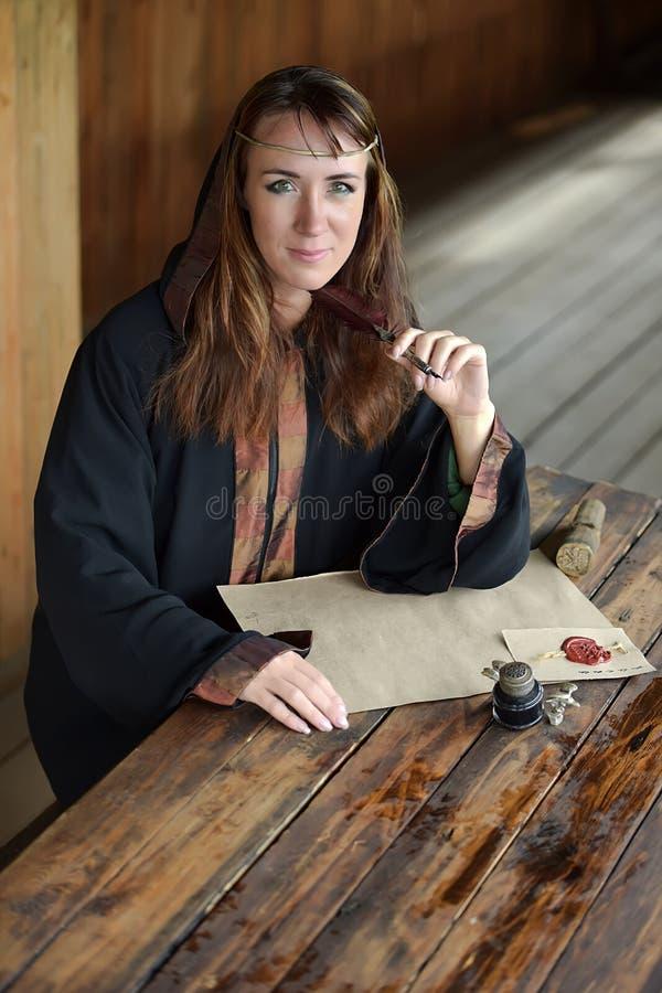 Kobieta w średniowiecznej pelerynie siedzi z piórem zdjęcia royalty free