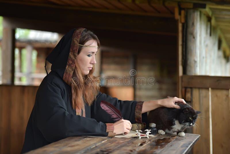 Kobieta w średniowiecznej pelerynie siedzi z piórem i pisze zdjęcia stock