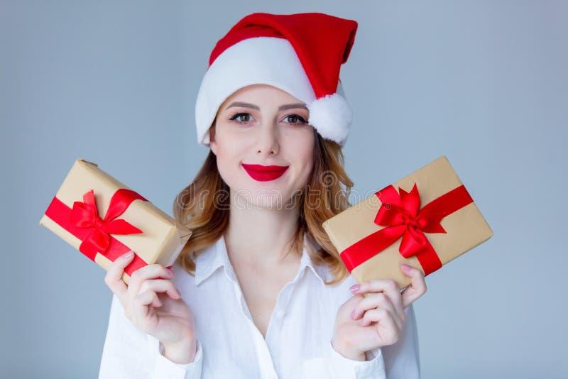Kobieta w Święty Mikołaj kapeluszu z Bożenarodzeniowym prezentem obrazy stock