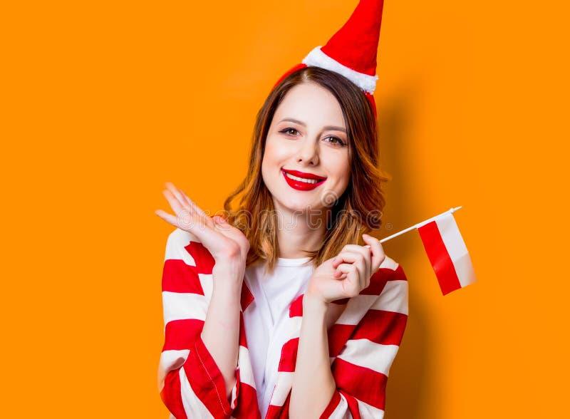 Kobieta w Święty Mikołaj kapeluszu z Polska flaga obrazy stock