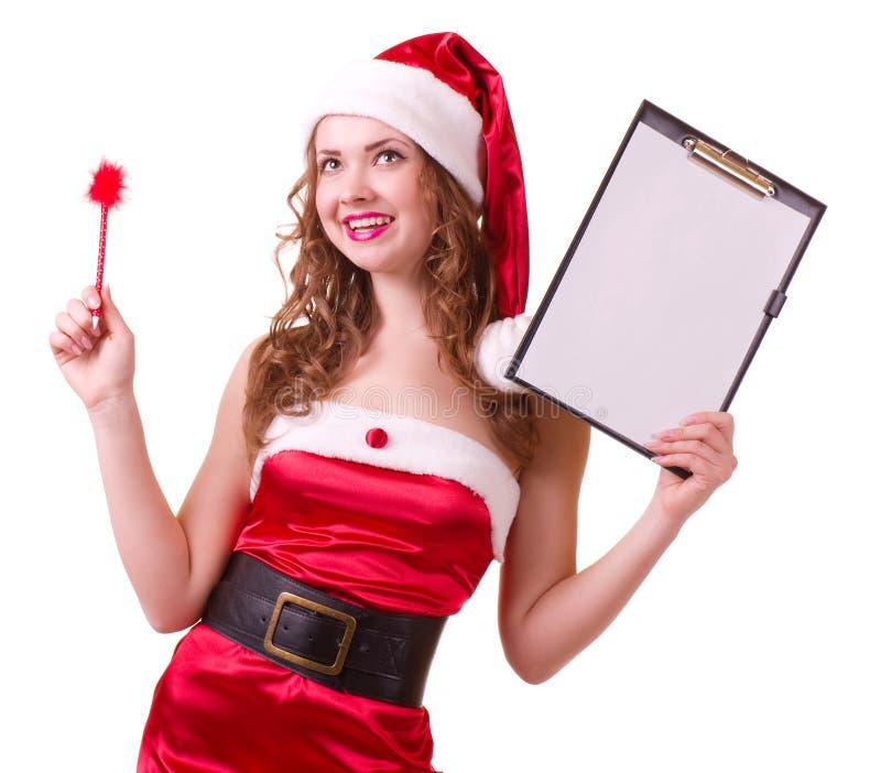 Kobieta w Święty Mikołaj ubraniach opiera na puste miejsce desce zdjęcie stock