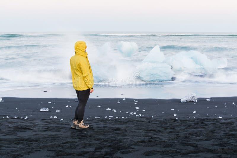 Kobieta w żółtej deszczowiec pozycji obok gór lodowych w arktycznym oceanie Iceland który dryfował z Jokulsarlon laguny, obrazy stock