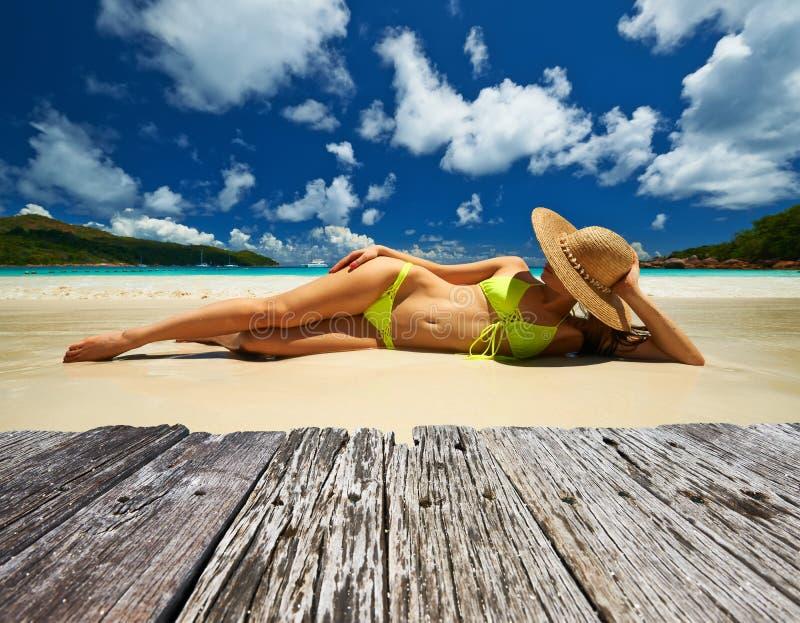 Kobieta w żółtym bikini lying on the beach na plaży przy Seychelles zdjęcie royalty free