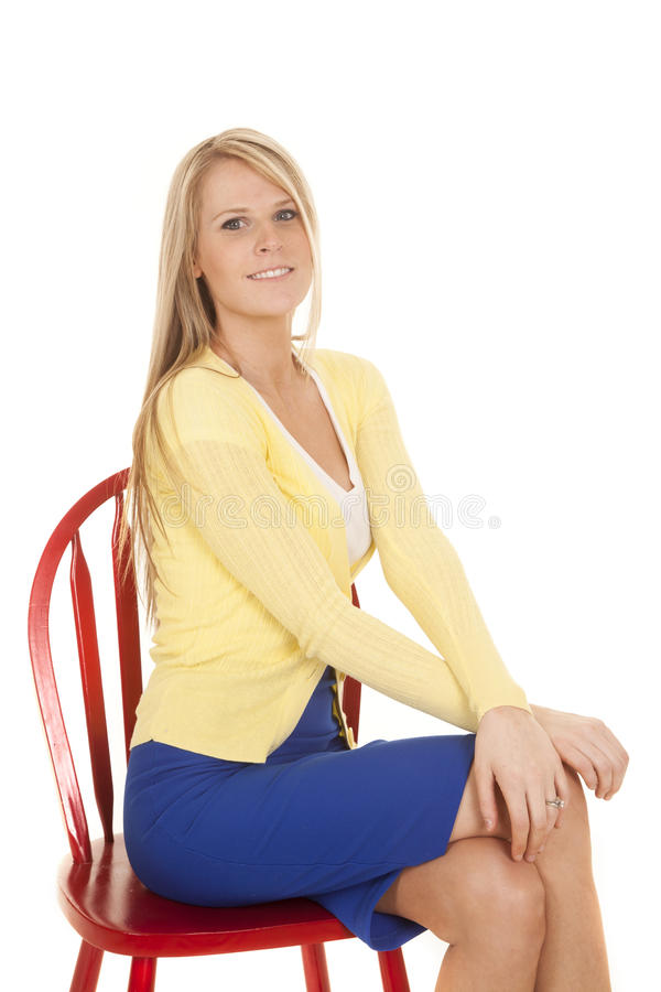 Kobieta w żółtym i błękitnym siedzi na czerwonym krześle fotografia royalty free
