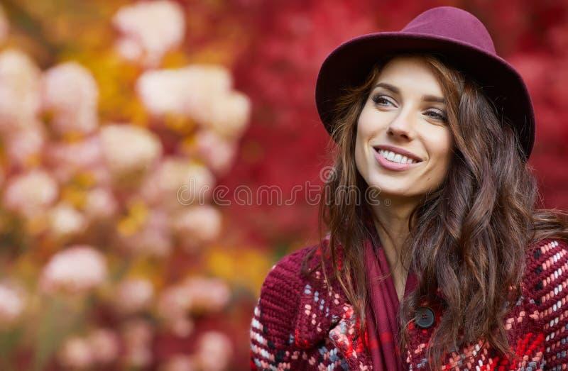 Kobieta w żakiecie z kapeluszem i szalikiem w jesień parku zdjęcia royalty free