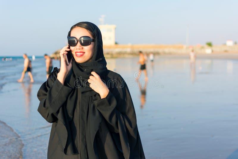 Kobieta w abaya używać telefon na plaży fotografia royalty free
