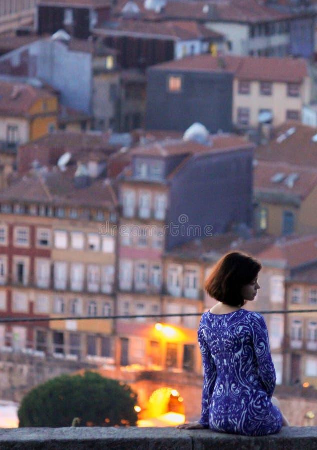 Kobieta w błękit sukni pozach dla fotografii przy półmrokiem z Porto w tle fotografia stock