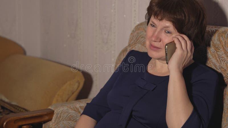 Kobieta w błękitnej sukni siedzi w krześle i opowiada na telefonie obraz stock