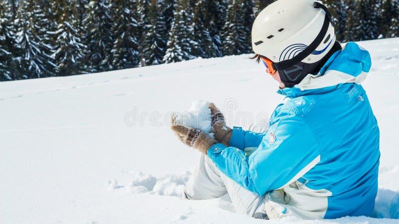 Kobieta w błękitnym narciarskim kostiumu i maska na górze halnego mienia śnieg w formie serca obrazy royalty free