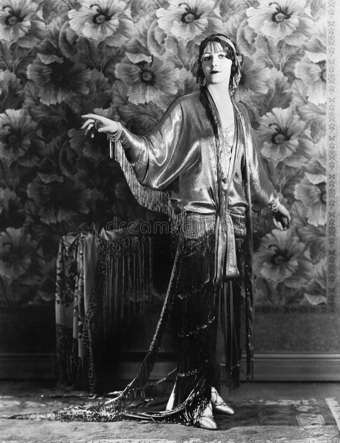 Kobieta w bardzo eleganckiej sukni pozyci przed kwitnącą ścianą (Wszystkie persons przedstawiający no są długiego utrzymania i ża zdjęcia stock