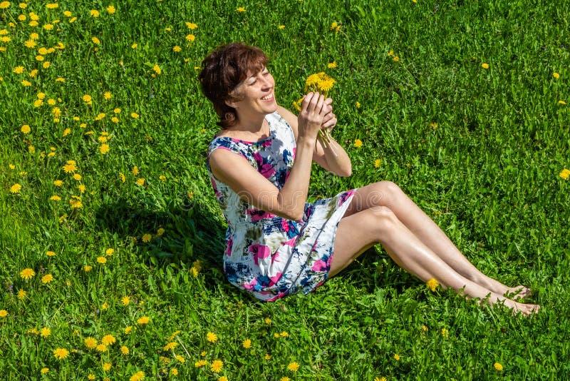 Kobieta w bawełnianej sukni siedzi na zielonej trawie z dandelions obraz stock