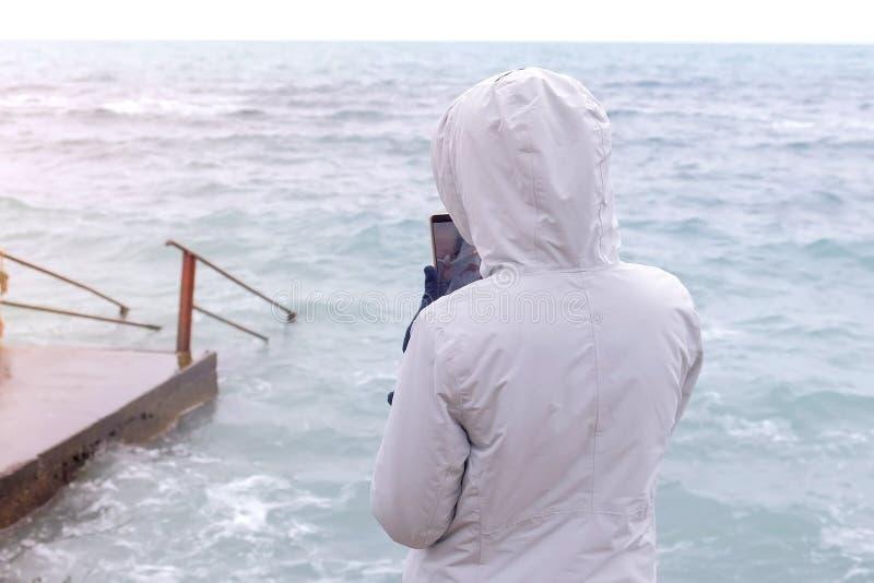 Kobieta w białej kurtce bierze telefonowi komórkowemu duże burz fale widok z powrotem fotografia stock