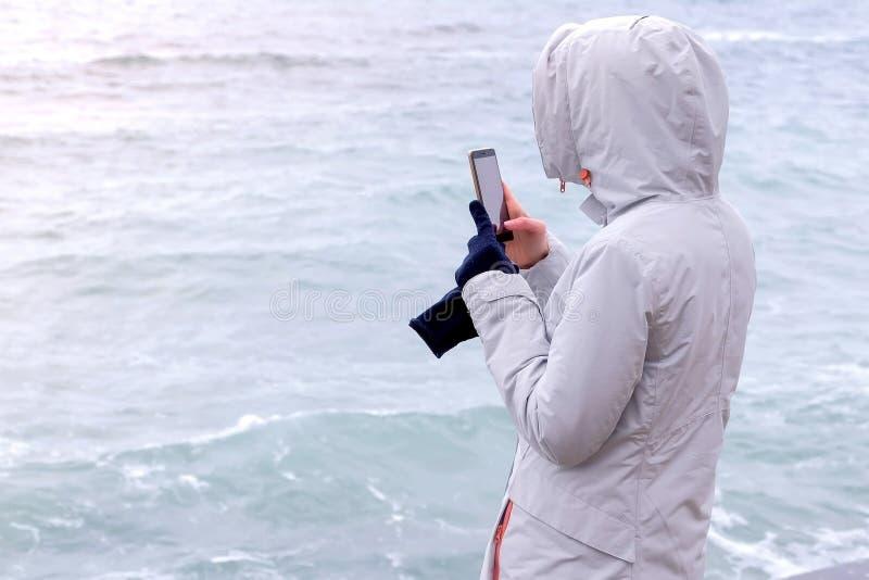 Kobieta w białej kurtce bierze telefonowi komórkowemu duże burz fale widok z powrotem fotografia royalty free