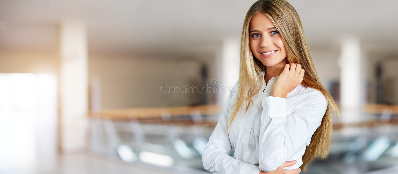 Kobieta w białej koszulowej pozycji w korytarzu centrum biznesu obraz royalty free
