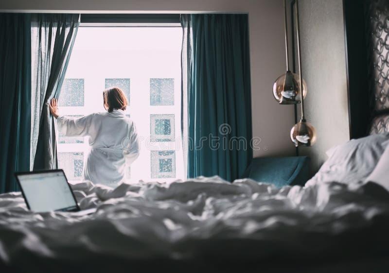 Kobieta w białym kontuszu pobycie słucha okno w pokoju hotelowym zdjęcie stock