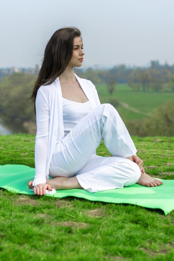 Kobieta w białym robi joga ćwiczeniu obrazy stock