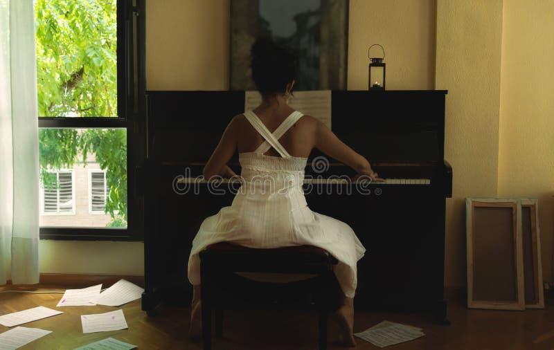 Kobieta w biel sukni bawić się pianino zdjęcia stock