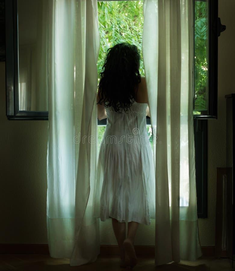 Kobieta w biel sukni przyglądającej out okno obraz royalty free