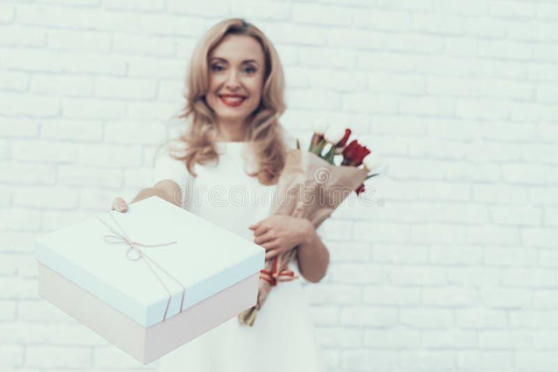 Kobieta w biel sukni z prezenta bukietem i pudełkiem fotografia stock