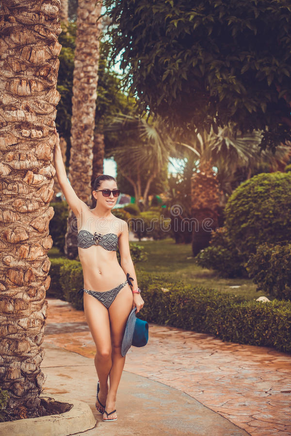 Kobieta w bikini pod palmą na ogrodowym tle obrazy stock