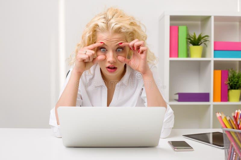 Kobieta w biurowym patrzeje komputerze i trzymać ona oczy otwieramy obraz stock