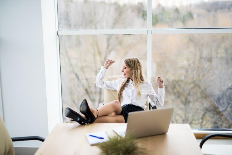 Kobieta w biurze relaksuje i podnoszący na duchu nastrój zdjęcie royalty free