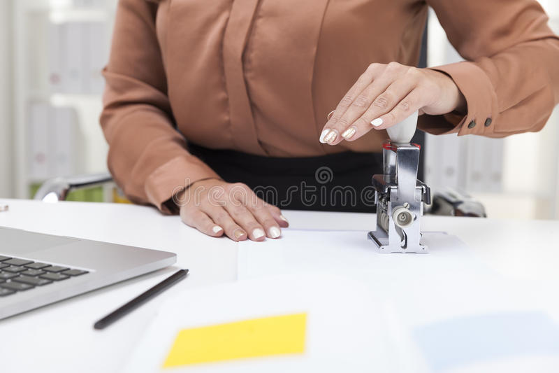 Kobieta w brown bluzce używa znaczek obraz royalty free
