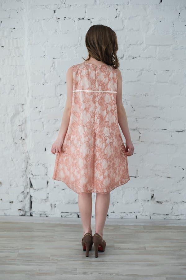 Kobieta w brzoskwini sukni przeciw białemu ściana z cegieł obrazy stock