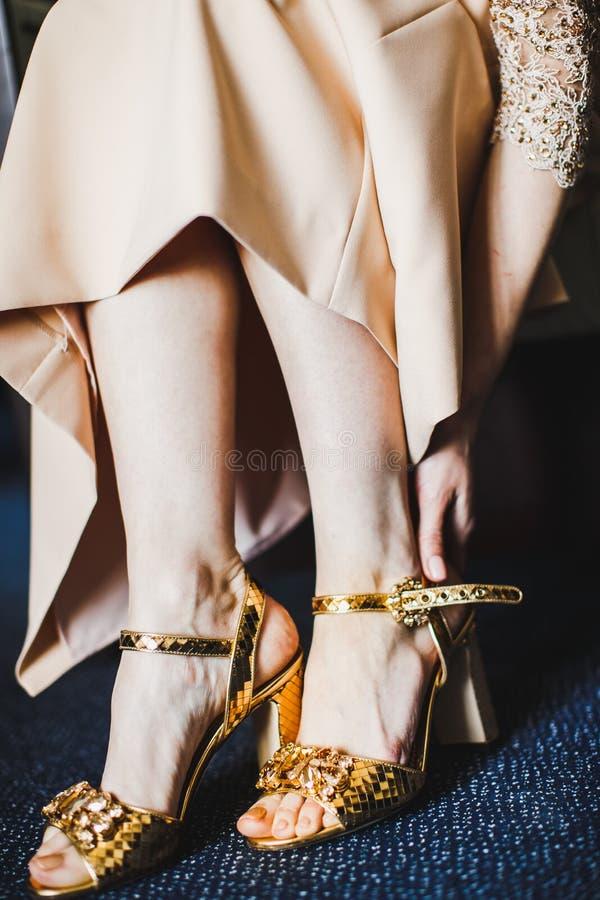 Kobieta w brzoskwini sukni stawia dalej jej złote szpilki fotografia stock