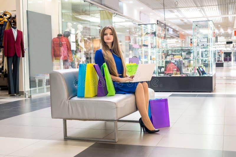 Kobieta w centrum handlowym robi online zakupy z laptopem obrazy royalty free