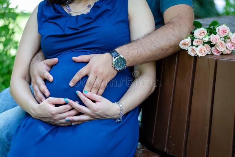 Kobieta w ciąży w błękitnej sukni i mężczyźnie w błękitnym tshirt obsiadaniu na ławce ściska kobieta w ciąży brzuszek zdjęcie royalty free