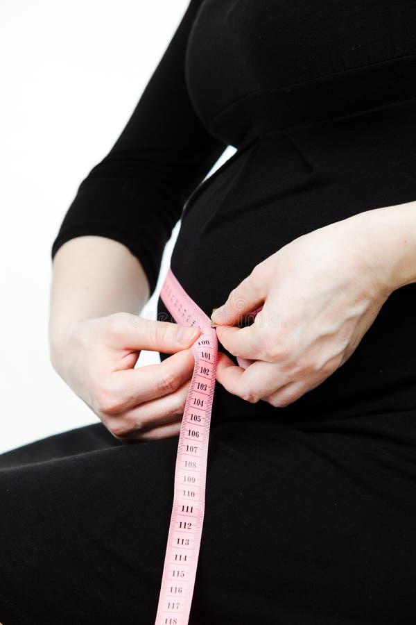 Kobieta w ciąży brzucha średnicy miara - czarna suknia zdjęcia royalty free