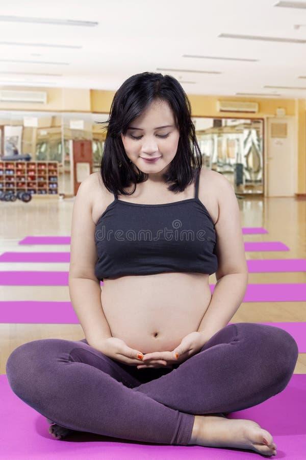 Kobieta w ciąży ćwiczy joga w sprawności fizycznej centrum zdjęcie royalty free