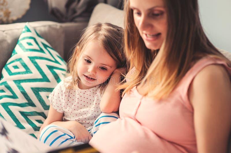 Kobieta w ciąży czytelnicza książka jej szczęśliwa berbeć córka w domu obrazy stock