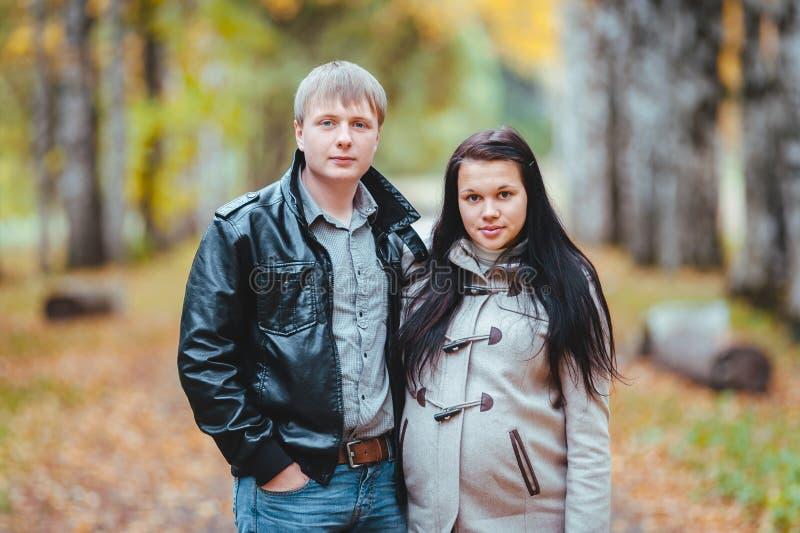 Kobieta w ciąży i jej męża odprowadzenie w jesień parku zdjęcia stock