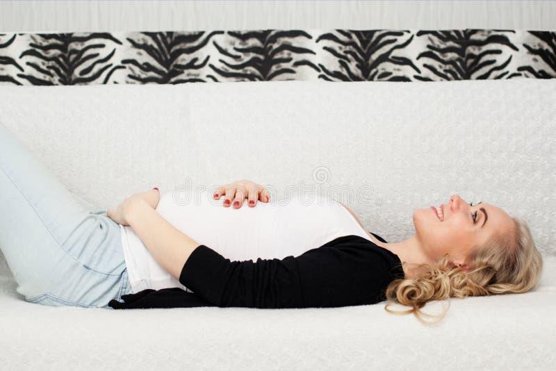 Kobieta w ciąży kłama na kanapie zdjęcia royalty free