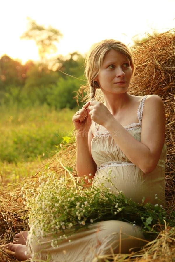Kobieta w ciąży na naturze blisko haystacks obraz royalty free