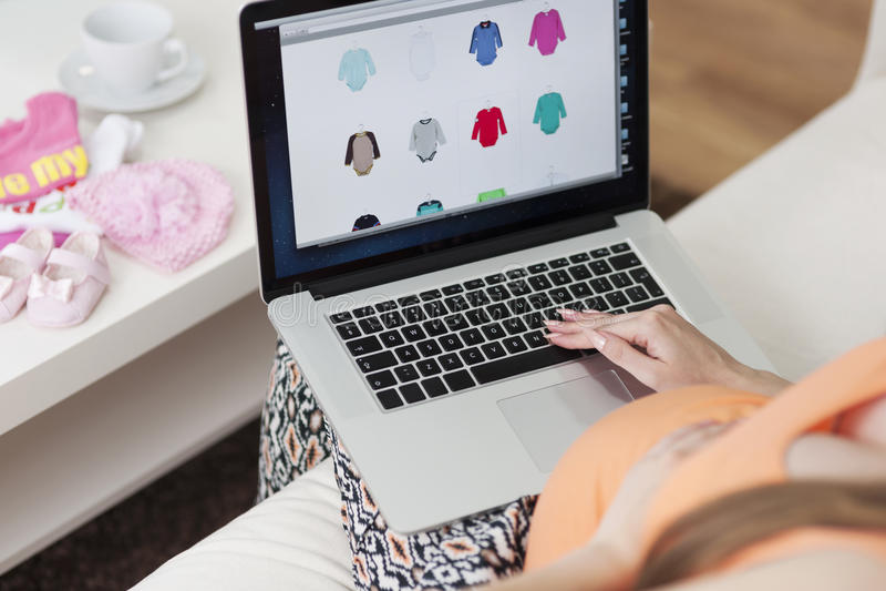 Kobieta w ciąży patrzeć odziewa dla dziecka zdjęcie stock