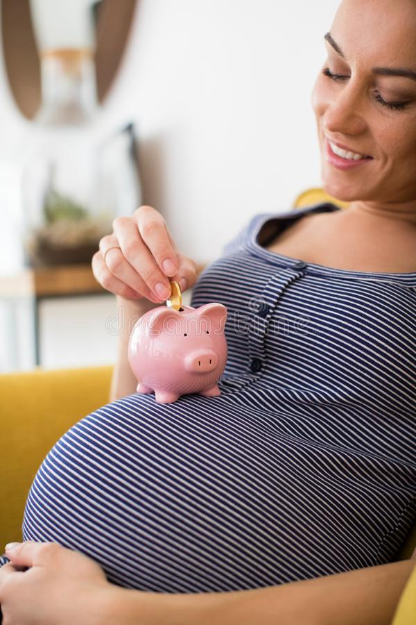 Kobieta W Ciąży W pepiniery kładzenia pieniądze W prosiątko banka Odpoczywać obraz royalty free