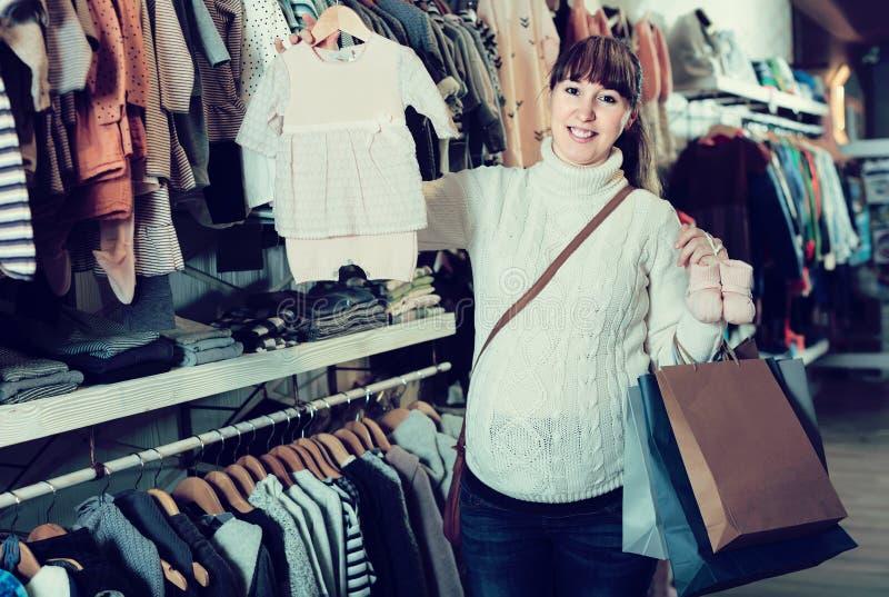 Kobieta w ciąży pokazuje jej zakupy w children's odzieżowym sho fotografia royalty free