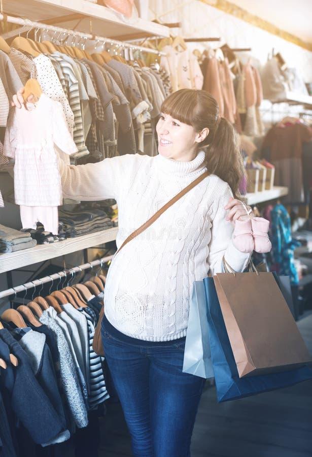 Kobieta w ciąży pokazuje jej zakupy w children's odzieżowym sho obraz royalty free