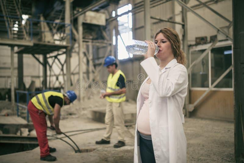 Kobieta w ciąży pracuje w budowy fabryce fotografia stock