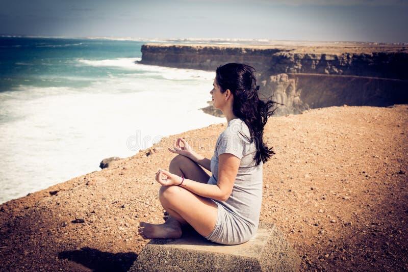 Kobieta w ciąży przy joga pozycją na oceanu wybrzeżu obraz royalty free